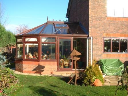 Victorian Conservatories - Five facet Victorian conservatory, mahogany effect PVCu with brick detail matching the house walls