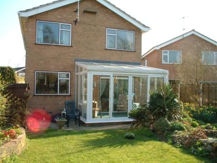 Sun Lounge Conservatories - White PVCu Sun Lounge Conservatory with four part sliding patio doors