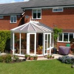 White PVCu Victorian conservatory with double doors on one facet