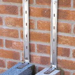 Conservatory building work showing steel wall ties fixing a conservatory base wall to the house